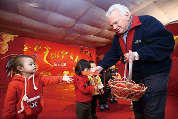 """Students at the Shengyin Kindergarten receive New Year's red envelopes from """"Father Grandpa"""" (Father Michelini)."""