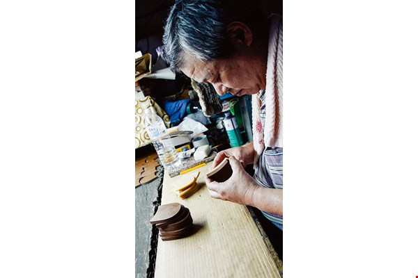 "A shoemaker glues on a rubber sole. Handmade shoes ""breathe"" better than  mass-produced ones because they don't have their entire soles slathered with glue.  (courtesy of Laney Shoes)"