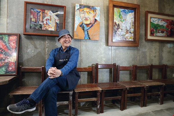 Hu Darfar's attire is almost always the same: fisherman's cap and blue jeans. The self-portrait behind him is the only portrait he has ever done. (photo by Jimmy Lin)