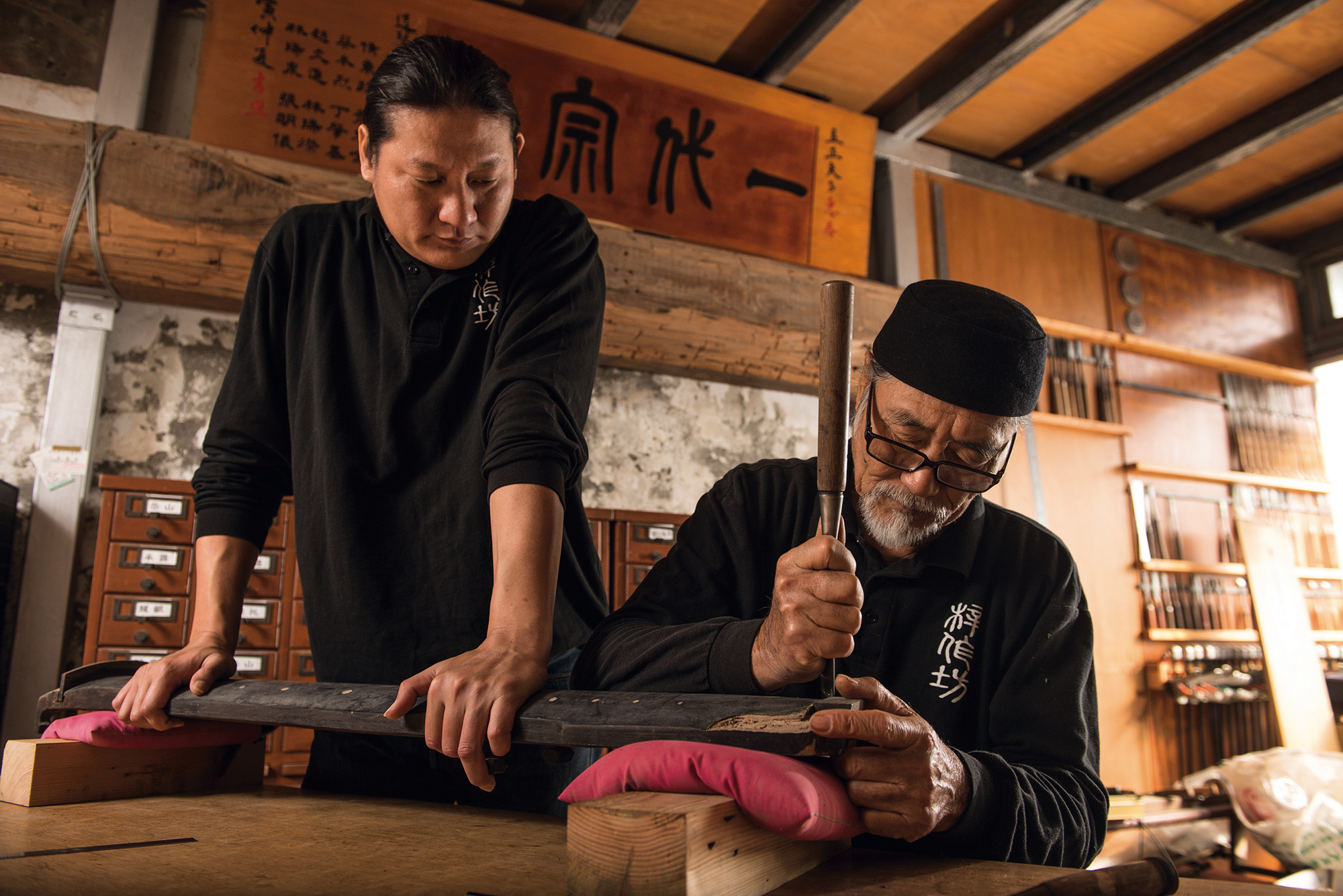 The inlaid corner ornaments at the end of this guqin have fallen off. Lin Li-cheng takes up his chisel to carefully repair the instrument, while his son Lin Fa helps by pressing down on it to hold it steady. Lin Fa grew up in just this way—sitting on guqin to press them down. (photo by Chuang Kung-ju)