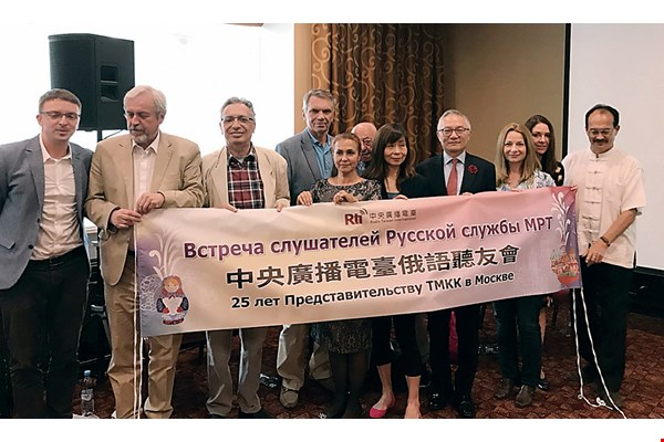 Lu Ping poses for a picture with Russian-language program hosts and audience members.