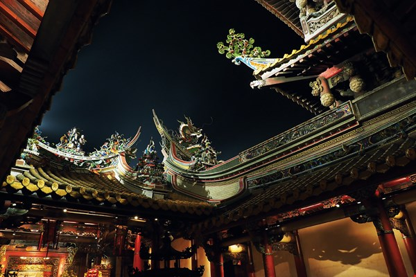 In the dark of night, light beams pick out the ceramic sculptures on the roof ridges of Beigang's Chao-Tian Temple, revealing their artistic splendor. (photo by Jimmy Lin)