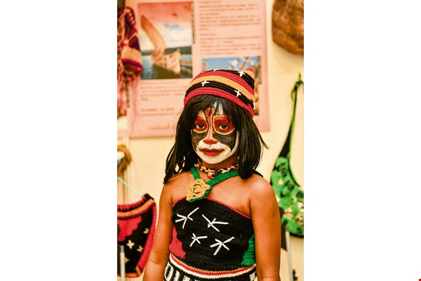 A family member of a diplomat from Papua New Guinea in eye-catchingly colorful face paint and attire. These are indispensable elements in song and dance performances at traditional festivals in that country.