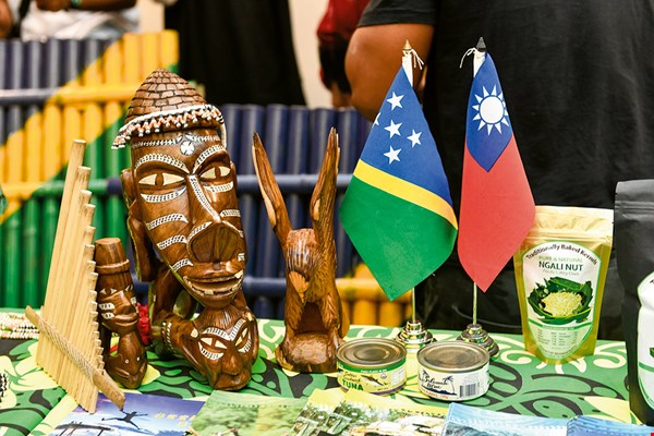 The photo shows wood carvings from the Solomon Islands, along with the ROC and Solomon national flags. The colors of the Solomon flag symbolize water and sky (blue), the sun (yellow), the land (green), and the country's original five (now six) provinces (white stars).