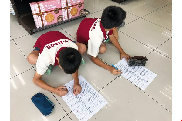 With children playing the role of store clerks, tutors at Zheng-Min Elementary lead them through a series of real-world challenges to test their ability to make two-step calculations. (courtesy of Zheng-Min Elementary School)