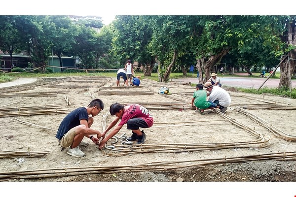 Ho oversees elementary and university students as they use bamboo to lay out paths through a patch of farmland. (courtesy of Hoch Ho)
