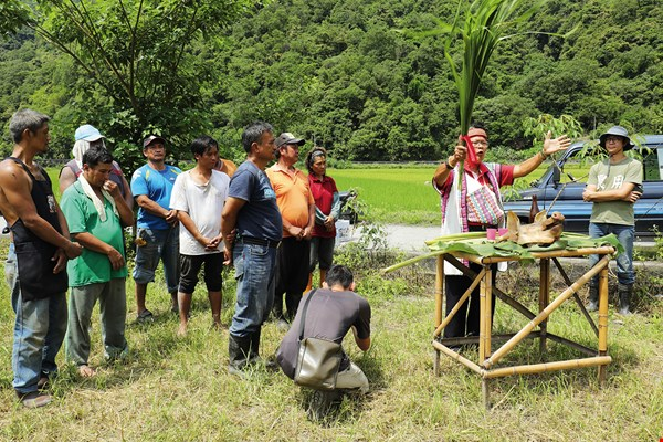 Amid assembled tribespeople, the chief offers blessings at the groundbreaking ceremony for a new village hall while Jian records the event. The scene captures the different roles that people play in the seed conservation movement.
