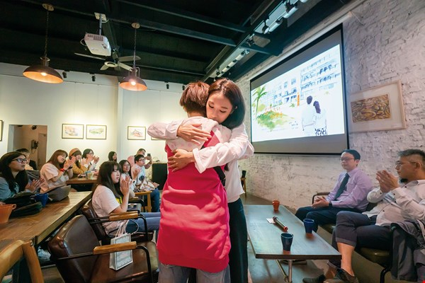 At a seminar on Light on a Cloudy Day, viewers share how life's pressures get them down. Actress Queenie Fang gives a hug to transmit positive energy. (photo by Lin Min-hsuan)