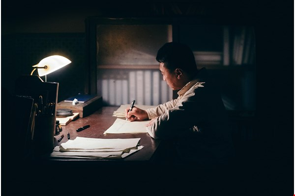 Throughout Survival, Loa Ho's literary works are read aloud to add a dramatic undertone. The photo shows a scene in which Loa Ho is writing in his clinic.